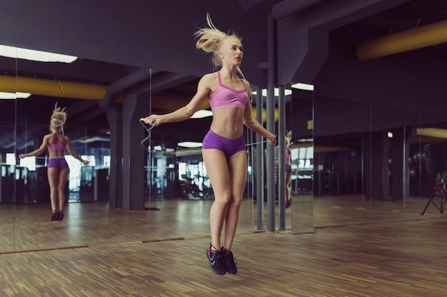 Silna i piękna wysportowana kobieta trenuje na siłowni