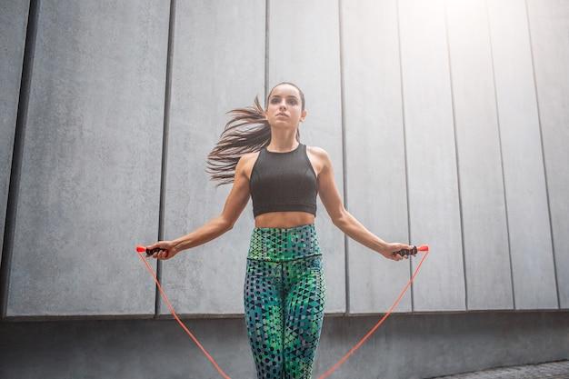 Silna i potężna młoda kobieta skacze z liny