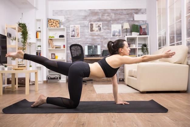 Silna kaukaska kobieta robi jogę dla równowagi w legginsach.