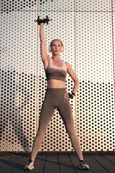 Silna kobieta ćwiczenia z hantlami na świeżym powietrzu przed ścianą i słuchanie muzyki w słuchawkach