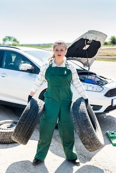 Silna kobieta, mechanik, pozuje z oponami w dłoniach