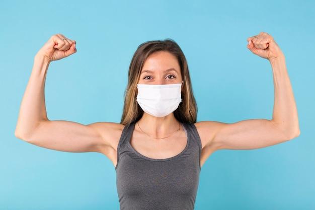 Silna kobieta pokazująca swoje mięśnie w masce medycznej
