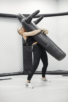 Silna kobieta trenuje z mężczyzną na kursie samoobrony na siłowni.
