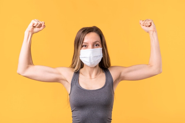 Silna kobieta z maską medyczną pokazując jej mięśnie