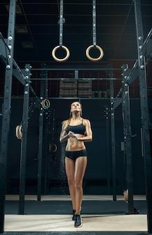 Silna lekkoatletka w stroju sportowym przygotowuje i chwyta kółka gimnastyczne podczas ćwiczeń na siłowni