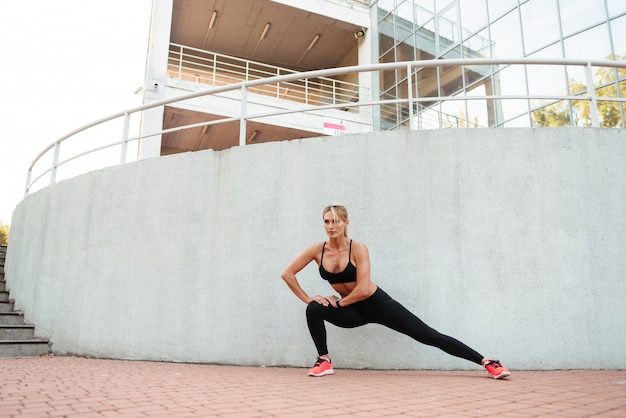 Silna młoda kobieta uprawia sport, aby sport rozciągał