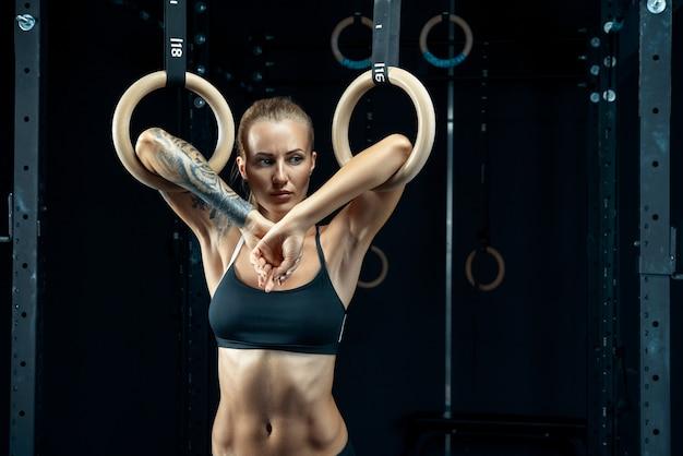 Silna młoda kobieta w czarnym sportowym topie trzyma kółka gimnastyczne na siłowni i patrzy w dół