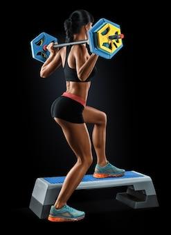 Silna młoda kobieta z atletycznego ciała robi ćwiczeniom ze sztangą