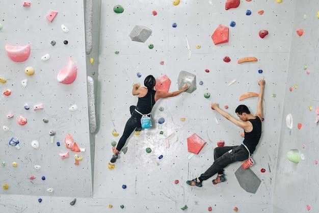 Silna młoda para trenuje w boulderingu, wspina się na sztucznej ścianie w pomieszczeniu