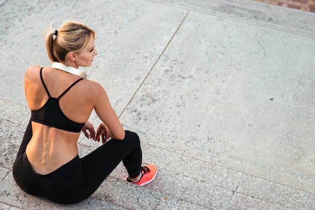 Silna młoda sport kobieta słucha muzyki w słuchawkach