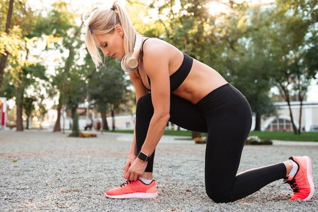 Silna młoda sportowa kobieta stoi outdoors wiązać koronki.