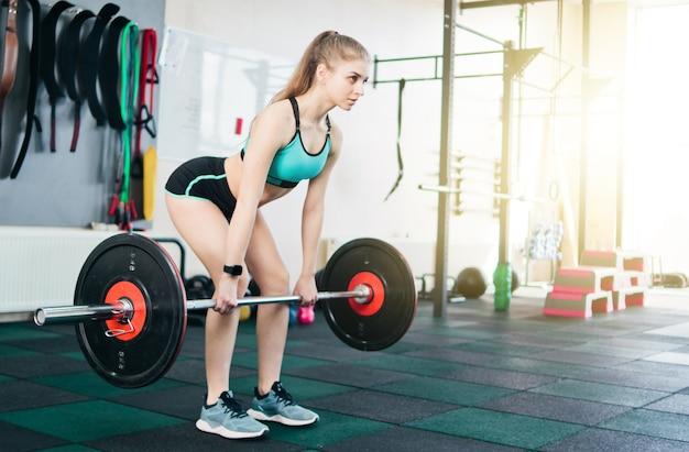 Silna, młoda, sprawna kobieta robi martwy ciąg ze sztangą na siłowni. wolny trening siłowy