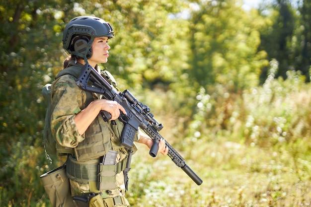 Silna odważna kobieta żołnierz armii z karabinem maszynowym stojąca w lesie