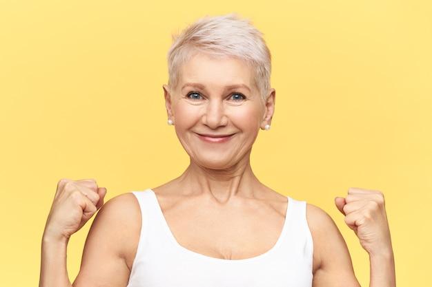 Silna pozytywna kobieta w średnim wieku z farbowanymi krótkimi włosami zaciskającymi pięści, pokazująca bicepsy, pozująca odizolowana. dojrzała blondynka o pewnym dumnym wyglądzie.