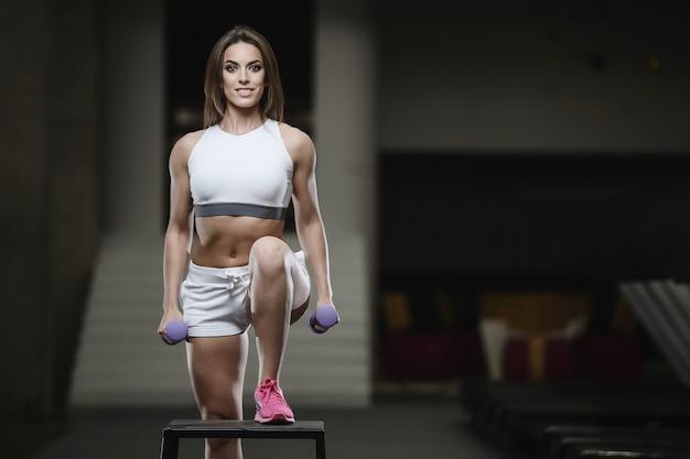 Silna seksowna sportowa młoda dziewczyna pracująca w gym out