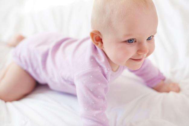 Silna śliczna mała dziewczynka zaczyna się czołgać