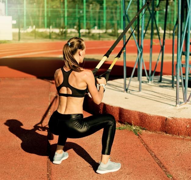 Silna, szczupła kobieta robi ćwiczenia z pasami fitness na torze stadionu z czerwoną powłoką w słoneczny, jasny dzień