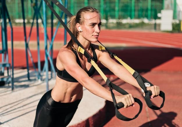 Silna szczupła kobieta robi ćwiczenia z paskami fitness na torze stadionu z czerwoną powłoką w słoneczny, jasny dzień