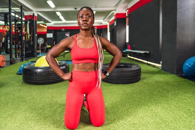 Silna, wysportowana czarna kobieta w sali gimnastycznej, gotowa i skoncentrowana na kolanach do uprawiania sportu, ubrana w czerwoną odzież sportową