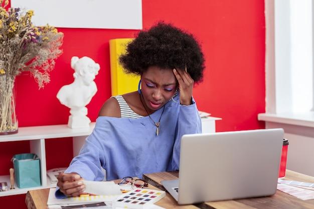 Silne bóle głowy. ciężko pracujący słynny młody artysta z silnym bólem głowy i zmęczeniem