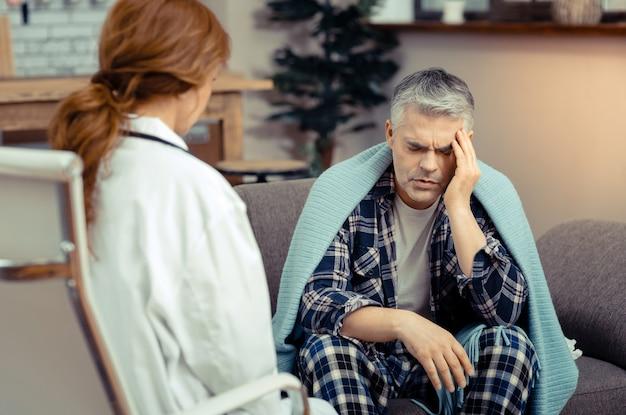 Silne bóle głowy. smutny, posępny mężczyzna dotykający skroni i skarżący się na ból głowy