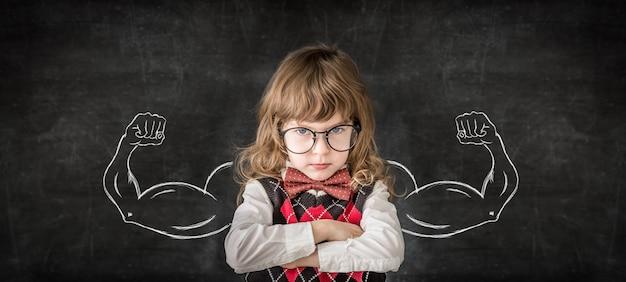 Silne dziecko w klasie. śmieszne dziecko przed tablicą. koncepcja edukacji
