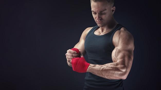 Silne kaukaski mężczyzna owija ręce na czarnym tle mężczyzna owija ręce czerwonymi okładami bokserskimi na czarnym tle silne dłonie i pięści, gotowe do treningu i aktywnego ćwiczenia