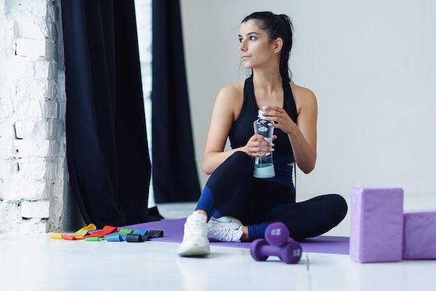 Silne kobiety w strojach sportowych siedzą na macie do jogi i piją wodę po treningu w domu