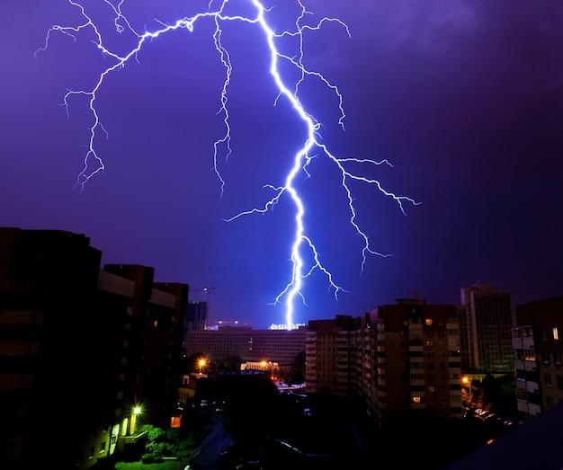 Silne wyładowanie pioruna nad sylwetkami domów podczas nocnej burzy nad miastem