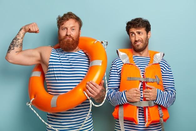 Silni faceci pozujący na plaży z kamizelką ratunkową i kołem ratunkowym