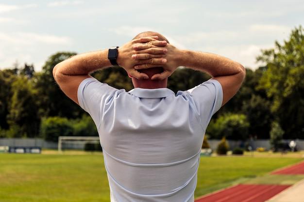 Silni łysi mężczyzna zostaje ręka na głowie w boisku piłkarskim