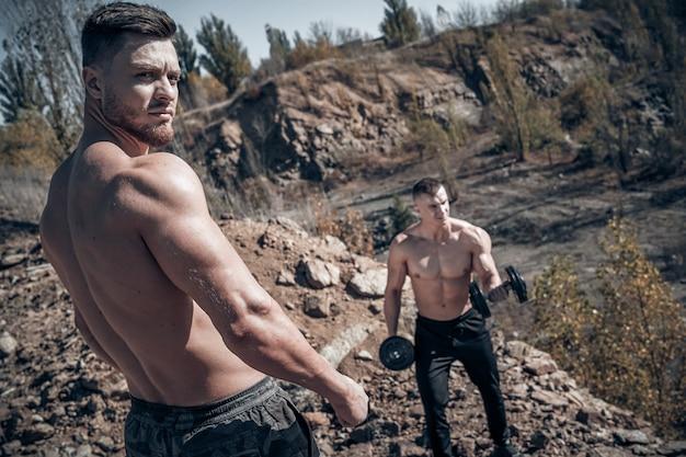 Silni mężczyźni robią trening na świeżym powietrzu. pozowanie z silnymi rękami. przystojni sportowcy. młodzi kulturyści. selektywne skupienie. skaliste tło. zbliżenie
