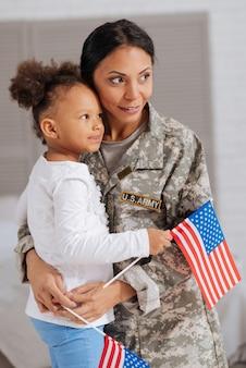 Silni razem. cudowne śliczne urocze panie przytulające się po dłuższym rozstaniu i trzymające w rękach flagi