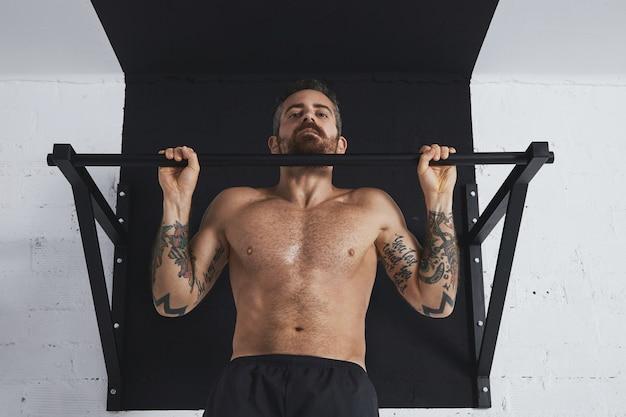 Silnie wytatuowany sportowiec topless pokazuje ruchy kalisteniczne w zbliżeniu do klasycznego podciągania w górnym pasku
