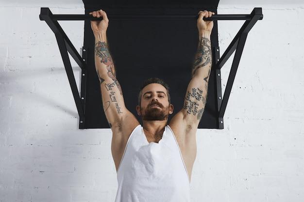 Silnie wytatuowany w białej koszulce bez etykiety czołg męski sportowiec pokazuje ruchy kalisteniczne z bliska klasycznego podciągania wiszący na drążku