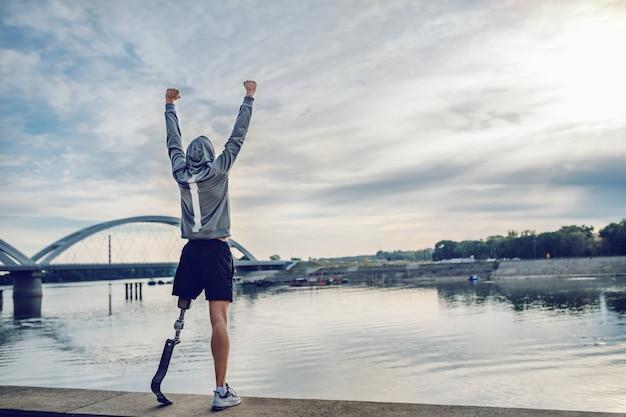 Silnie zmotywowany niepełnosprawny sportowiec rasy kaukaskiej w odzieży sportowej ze sztuczną nogą, stojący na nabrzeżu i trzymający ręce w górze.