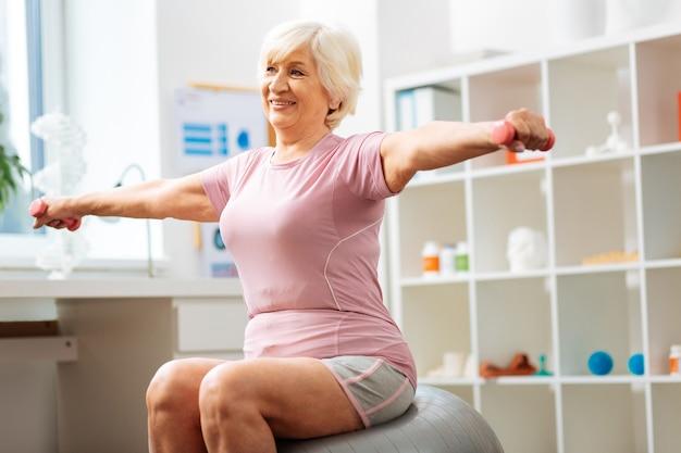 Silniejsze mięśnie. wesoła pozytywna kobieta uśmiechająca się podczas ćwiczeń z hantlami