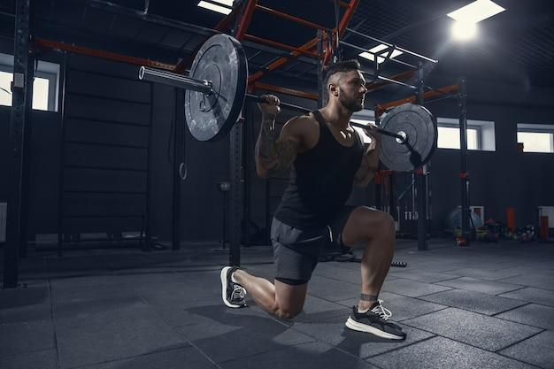 Silniejszy, młody muskularny sportowiec rasy kaukaskiej ćwiczy wypady w siłowni ze sztangą. model wykonujący ćwiczenia siłowe, trenujący dolną część ciała. wellness, zdrowy styl życia, koncepcja kulturystyki.