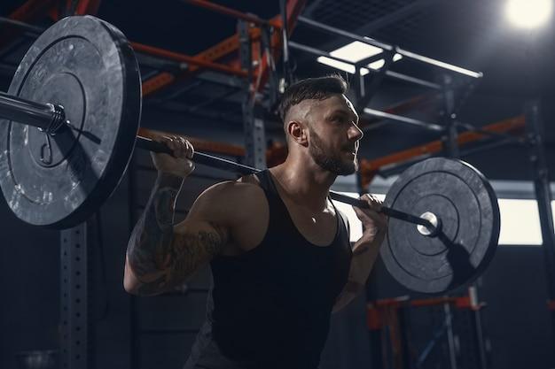 Silniejszy, młody, muskularny sportowiec rasy kaukaskiej wykonujący wypady na siłowni ze sztangą. model mężczyzna robi ćwiczenia siłowe, trenuje dolną część ciała. wellness, zdrowy styl życia, koncepcja kulturystyki.