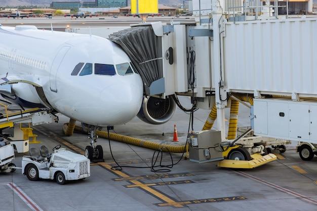 Silnik odrzutowy przeciwko średniej wielkości samolotowi na lotnisku podczas załadunku samolotu na międzynarodowym lotnisku