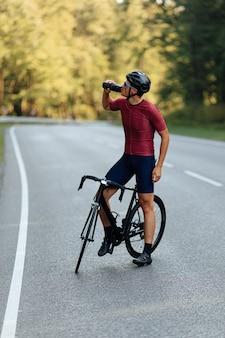 Silny, aktywny mężczyzna w odzieży sportowej i kasku ochronnym pije wodę z butelki, stojąc na utwardzonej drodze z czarnym rowerem