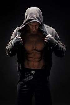 Silny, atletyczny mężczyzna, model fitness pokazujący sześciopak abs