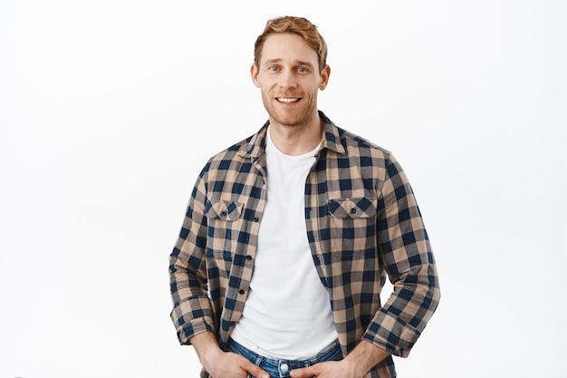 Silny, atrakcyjny facet z rudymi włosami, patrzący z przodu, pozujący na białej ścianie