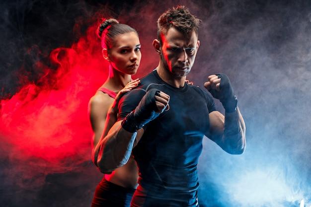 Silny bokser w postawie z rękoma na pięści z dziewczyną stojącą za nim.