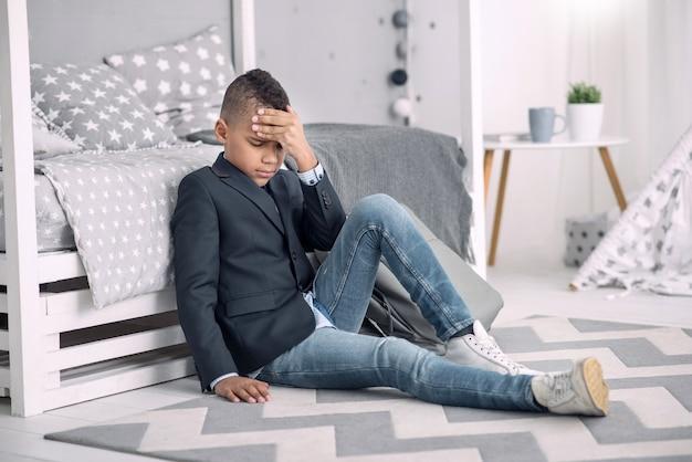 Silny ból głowy. zdenerwowany chłopiec afroamerykański dotykając jego czoła, siedząc na podłodze w domu
