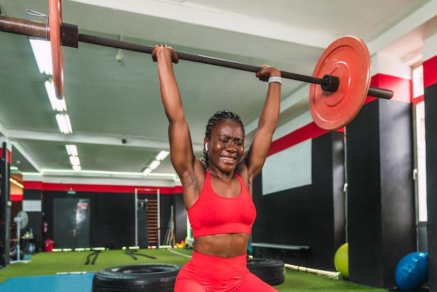 Silny czarnoskóry atleta w sali gimnastycznej wykonujący ćwiczenia ze sztangą i podnoszenie ciężarów na wzmocnienie barków i bicepsów wykazujący duży wysiłek i w czerwonym stroju sportowym