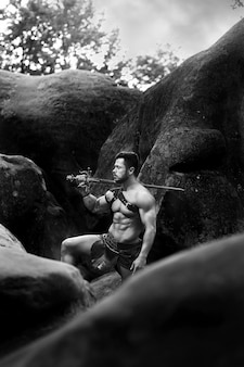 Silny człowiek. monochromatyczne pionowe ujęcie spartańskiego wojownika odpoczywającego w pobliżu skał w lesie z mieczem na ramieniu