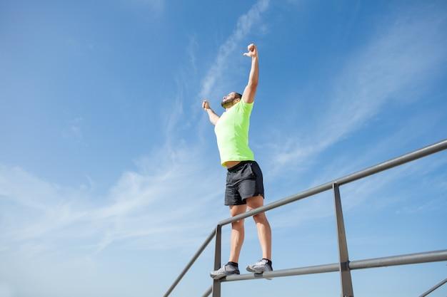 Silny człowiek świętuje sukces sportu na zewnątrz