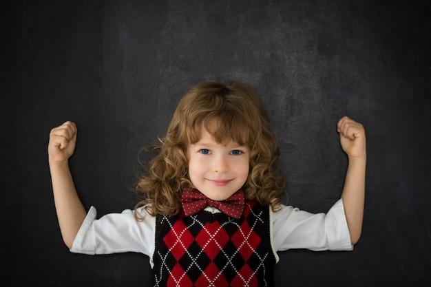 Silny dzieciak w klasie. szczęśliwe dziecko przed tablicą. koncepcja edukacji