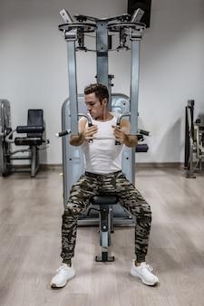 Silny facet robi ćwiczenia ramion na maszynie